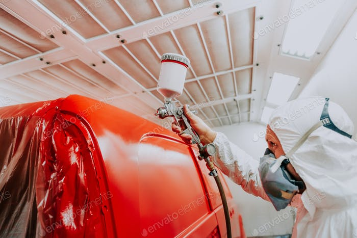 Close up of automobile mechanic worker painting a red car with spray gun