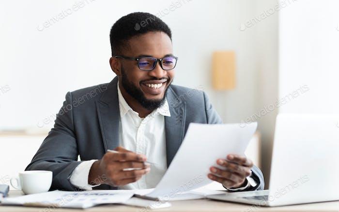 Fröhlicher schwarzer Geschäftsmann überprüft Berichte und macht Notizen