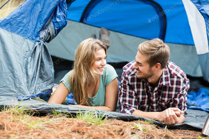 Young pretty hiker couple lying in a tent in the nature