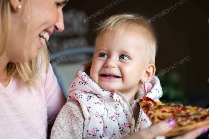 Kleines Mädchen isst eine große Scheibe Pizza aus den Händen ihrer Mutter. Kinderpizza