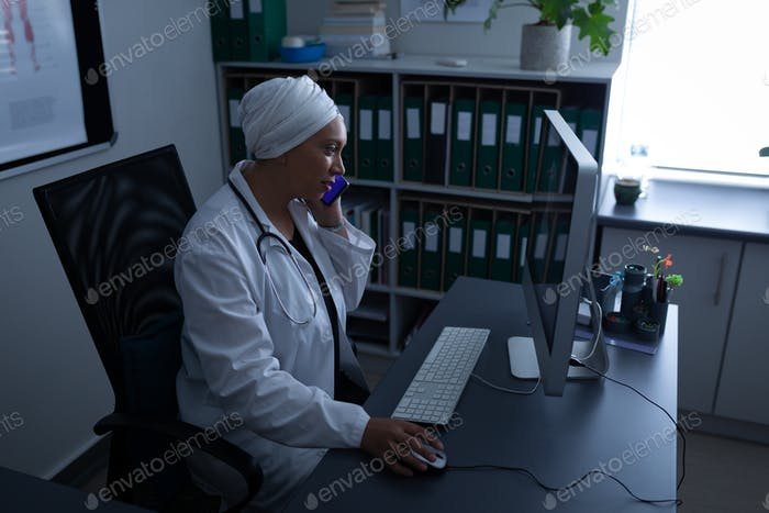 Female doctor talking on mobile phone while working with computer in office at hospital