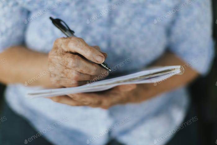 Senior woman writing down her memories into a notebook