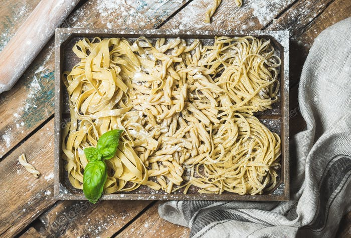 Homemade uncooked Italian pasta in wooden tray over shabby background