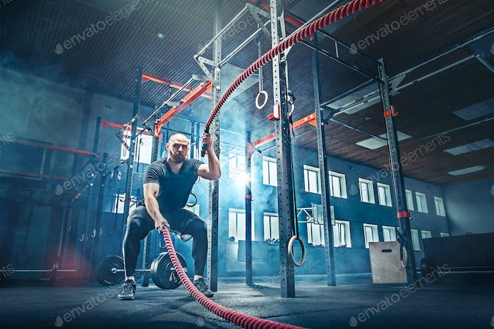Men with battle rope battle ropes exercise in the fitness gym.