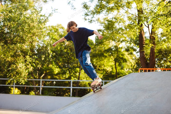 Young guy in T-shirt skateboarding and practicing stunts while s