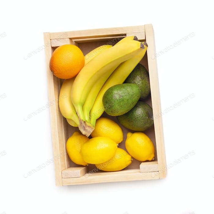 Frische und ökologische Früchte in Holzkiste isoliert auf weiß