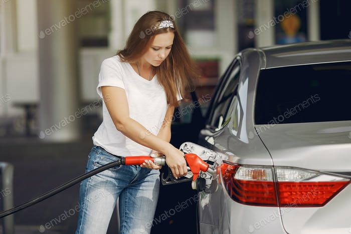 Elegant woman standing on a gas station