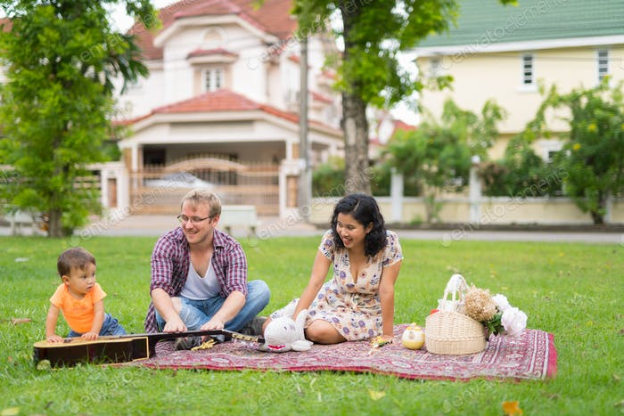 Portrait of happy multi-ethnic family bonding together outdoors