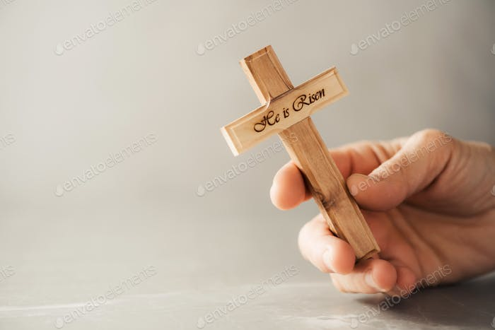 Hands holding wooden christian cross with text He is risen on grey background. Reminder of Jesus