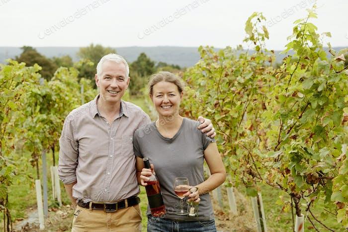 Una pareja, fundador del viñedo y su pareja de pie entre las hileras de vides.