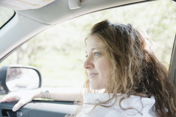 Woman seated in the front seat of a car.