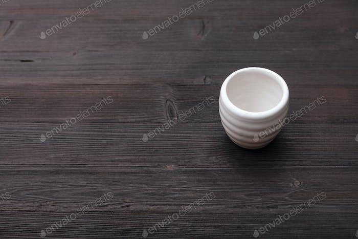 weiße Tasse für Sake auf dunkelbraunem Holztisch