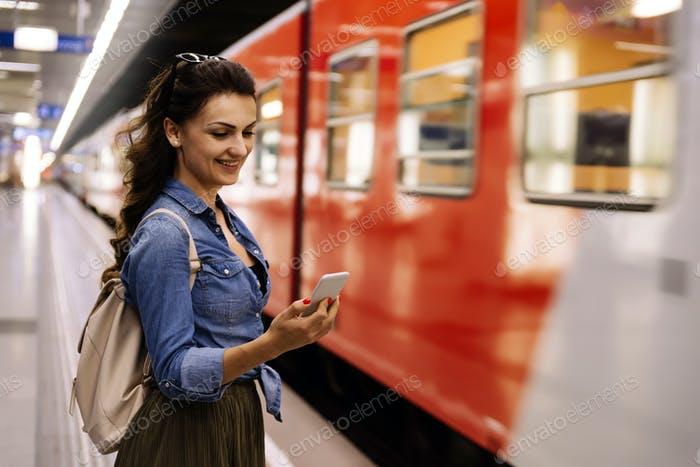 Beautiful woman using her cell phone on subway platform.