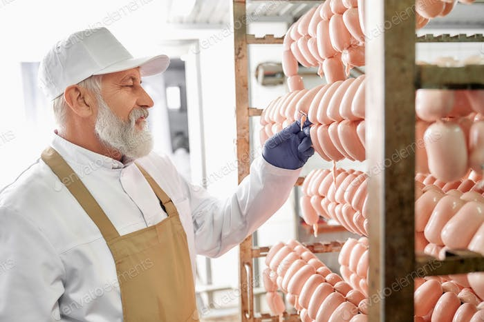 Meat factory production worker observing sausages