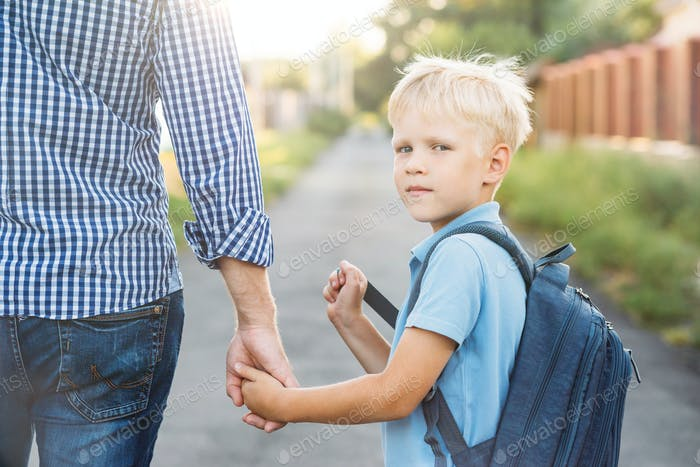 Little Boy with School Bag Looking at Camera.