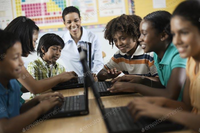 Eine Gruppe von Schülern, die Laptops in einer Lektion verwenden.
