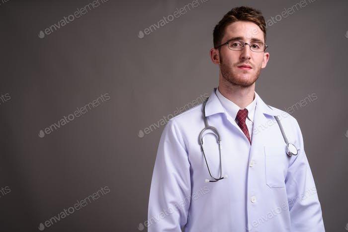 Young handsome man doctor wearing eyeglasses against gray backgr