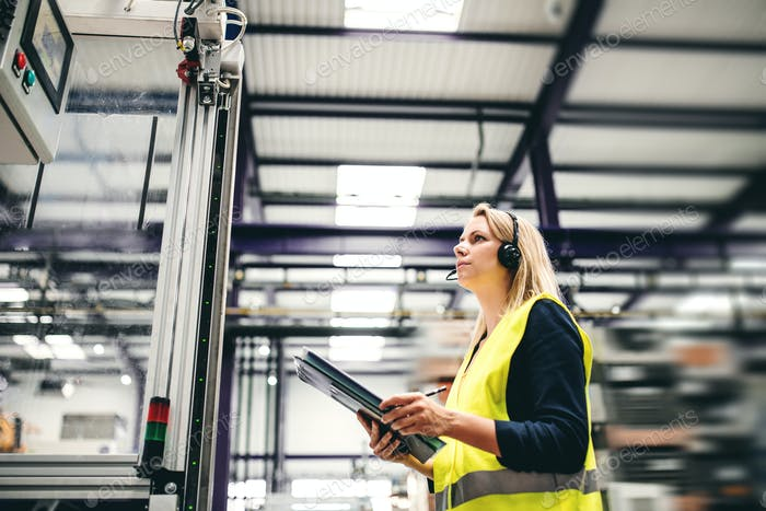 An industrial woman engineer with headset and clipboard in a factory, working.