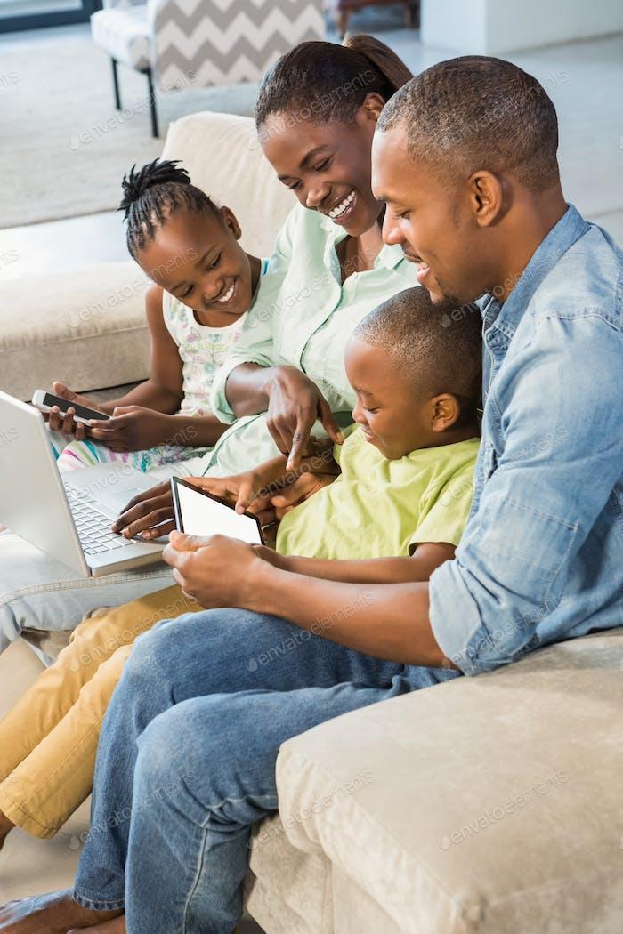 Glückliche Familie mit Technologie zusammen im Wohnzimmer