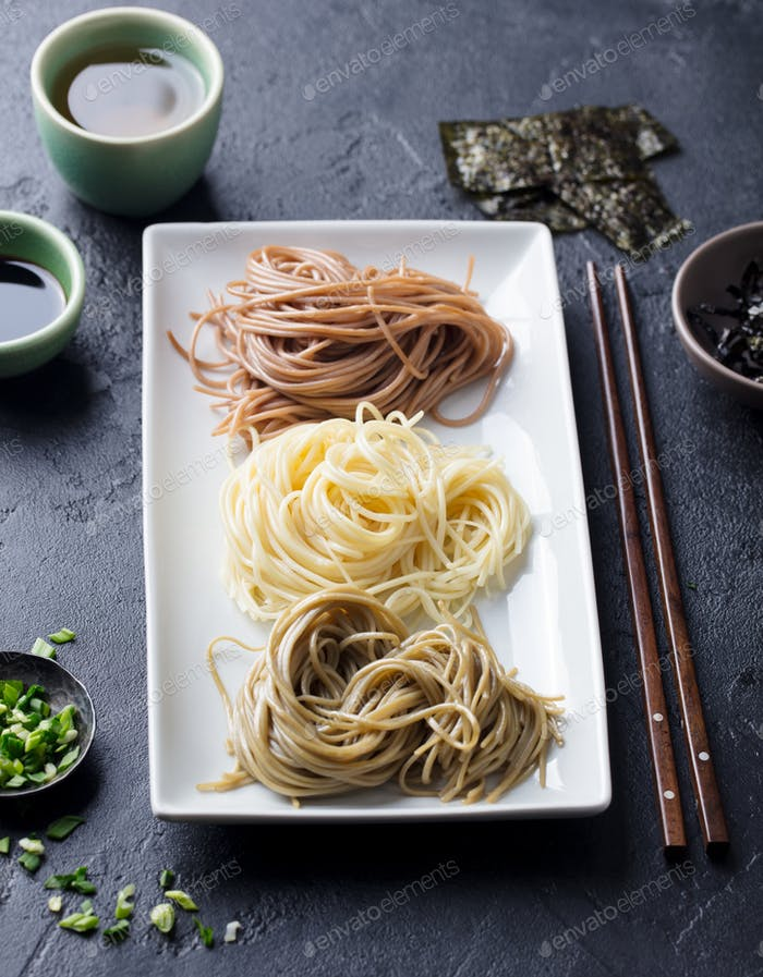 Assortment of Japanese Soba Noodles with Sauce and Garnishes. Black Slate Background.