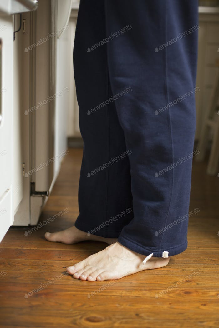 Barefoot man standing in a kitchen.