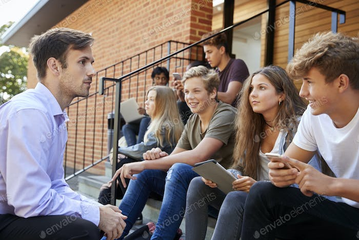Teenage Students Talking To Teacher Outside School Buildings