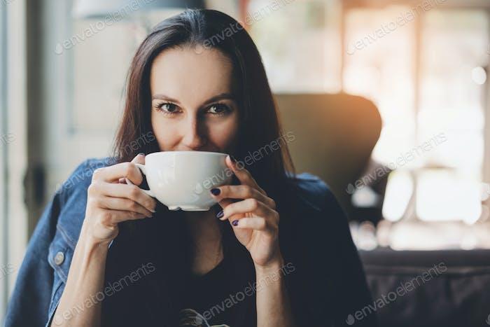 Mädchen trinken frisches heißes Getränk im Café