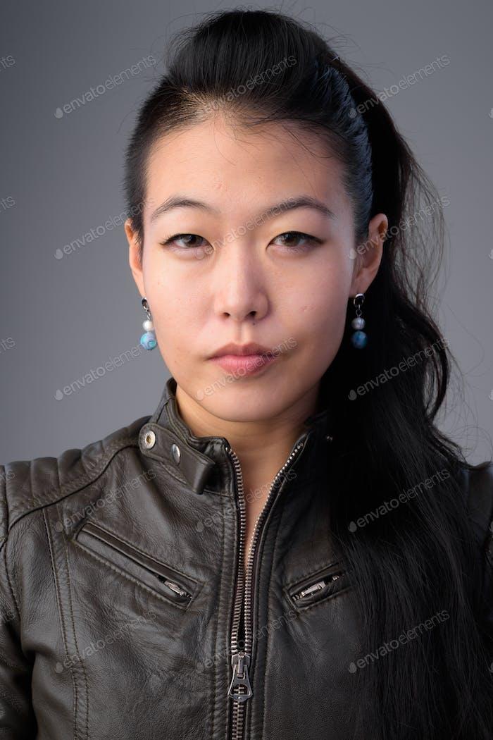 Gesicht der schönen asiatischen rebellischen Frau mit Lederjacke
