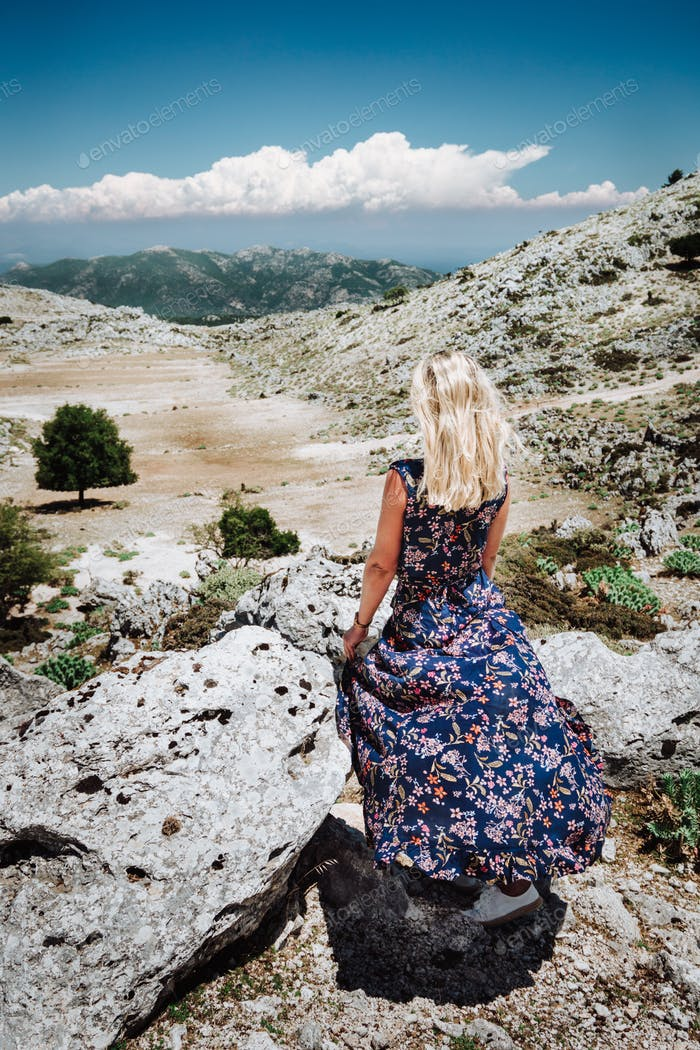 Tanned girl in front of panorama of highland countryside and beautiful nature. Rocky stones and