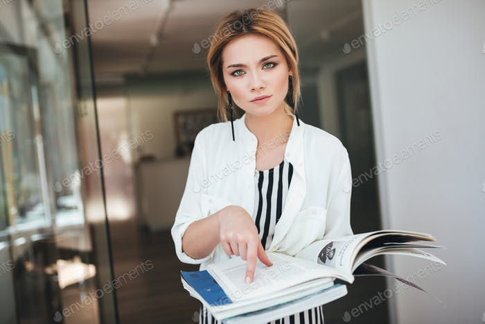 Girl in white shirt thoughtfully looking in camera and showing something in her book