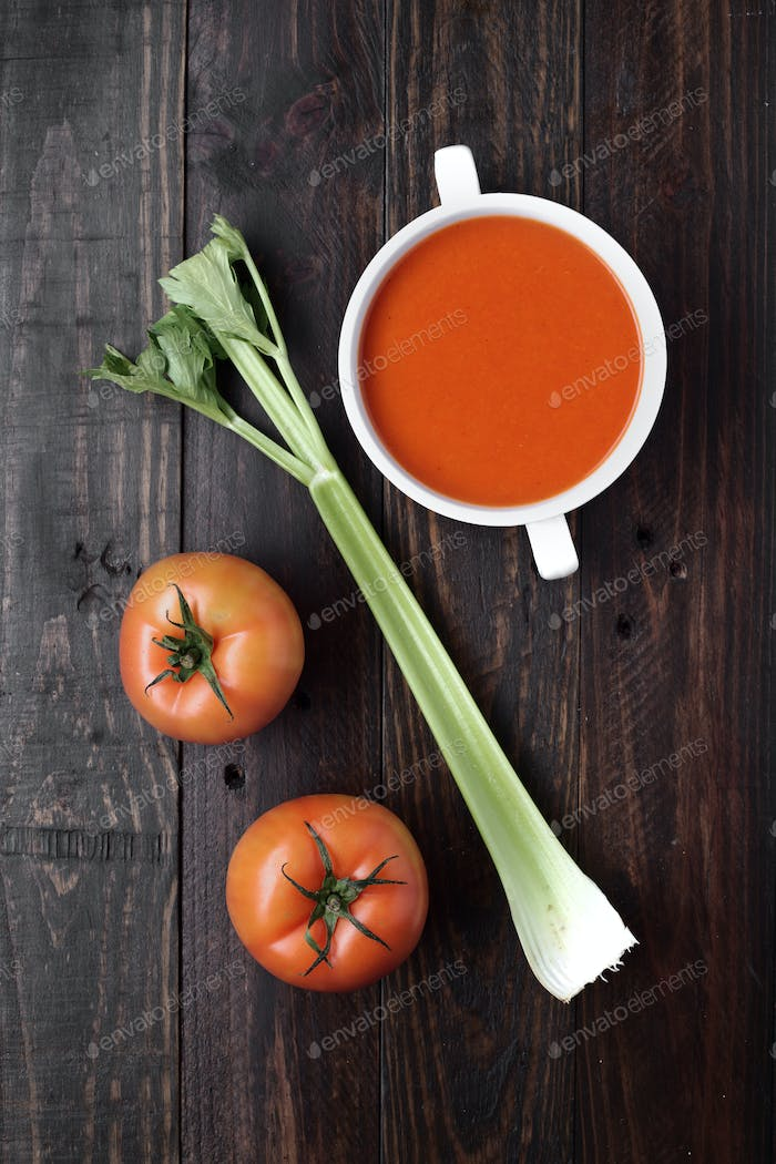 branch of celery and bowl of tomato sauce on rustic wood with natural light