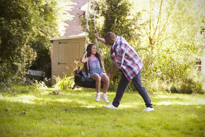 Father Pushing Daughter On Tire Swing In Garden