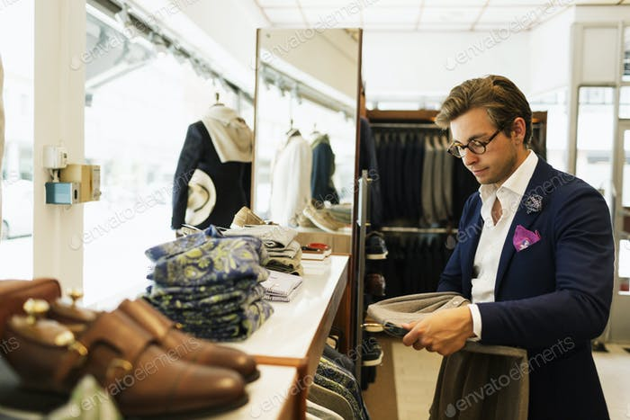Sales clerk looking at t-shirt in clothing store