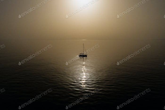 Aerial view of yacht in the sea with beautiful sunrise