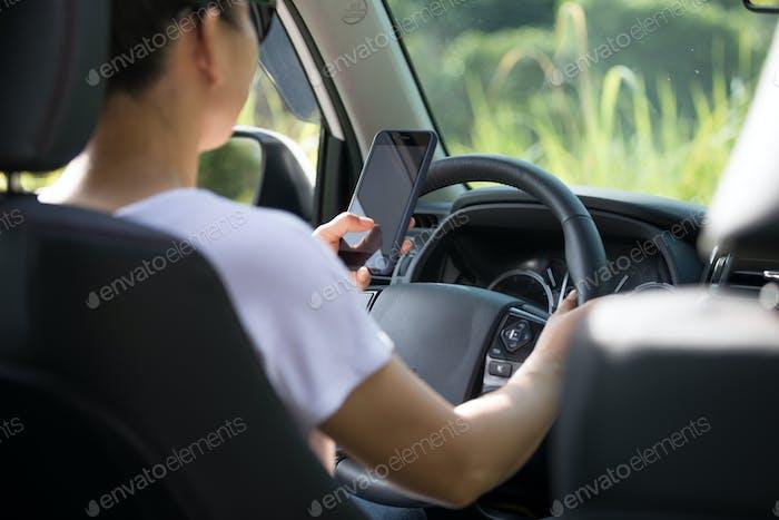 FahrenFrau Fahrer mit Smartphone während der Fahrt ein Off-Road-Auto in der Natur
