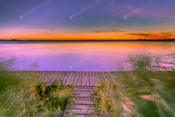 Langzeitbelichtung Bild von Lila Sonnenuntergang über der Promenade am Ufer