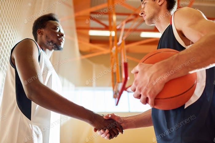 Serious basketball players from different team shaking hands