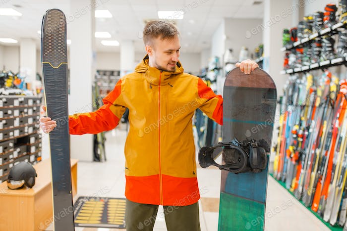 Man choosing downhill ski and snowboard, shopping