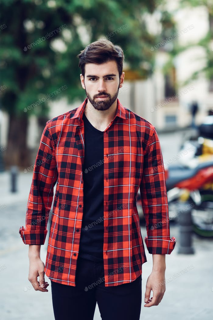 Young bearded man, model of fashion, in urban background wearing