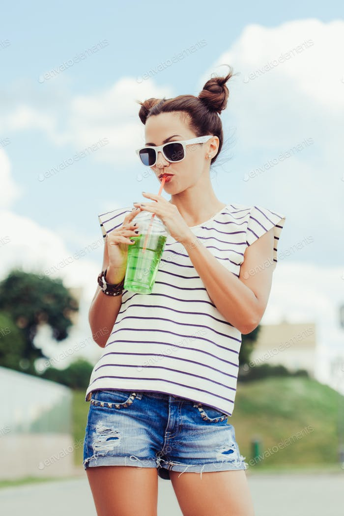 Funky girl drinking water against the sky
