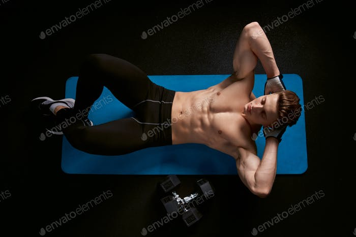 Shirtless man training abs on mat