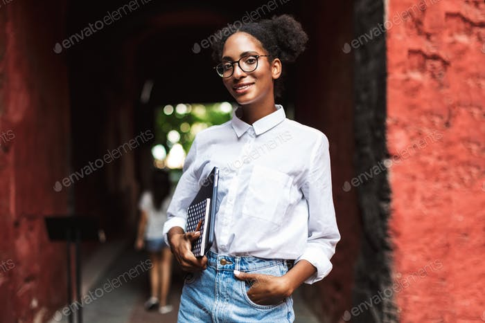 Pretty smiling african girl in eyeglasses and shirt holding lapt