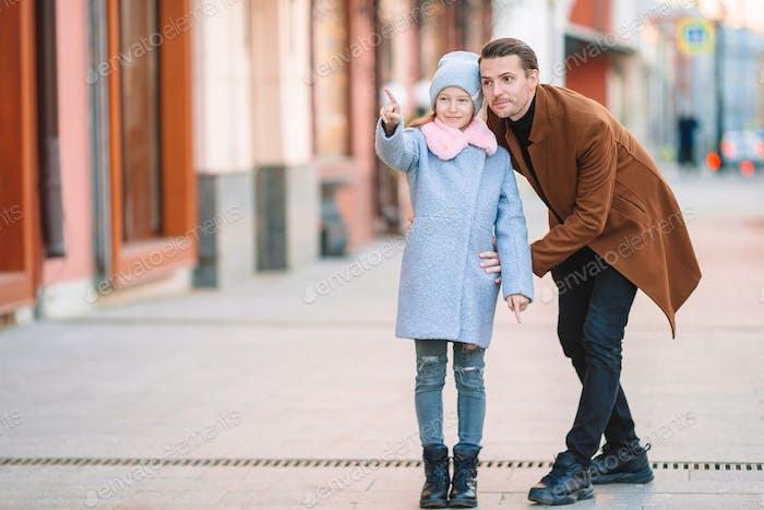Glücklicher Vater und kleine entzückende Mädchen in die Stadt im freien