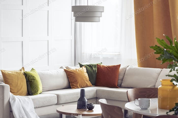 Lamp above table in bright living room interior with yellow pill