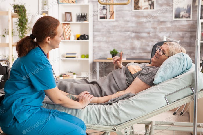 Old woman laying in bed in a nursing home talking with female doctor