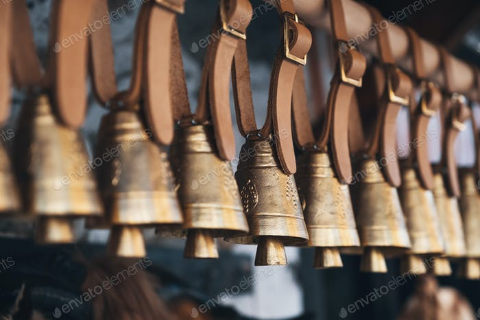 Brass bells hanging outside on leather straps