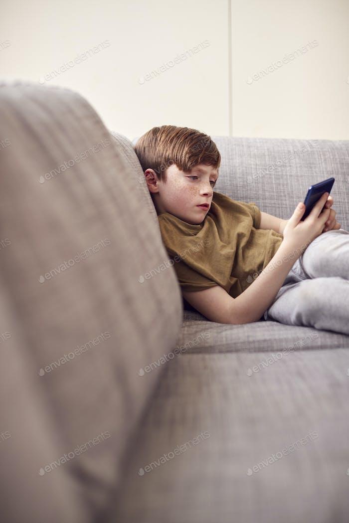 Niño sentado en el sofá en casa juegos en casa en dispositivos de mano en casa