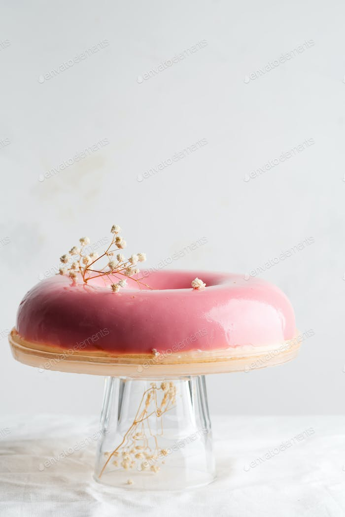 Freshly cooked homemade strawberry fruit glazed pink dessert on a glass dish against light grey