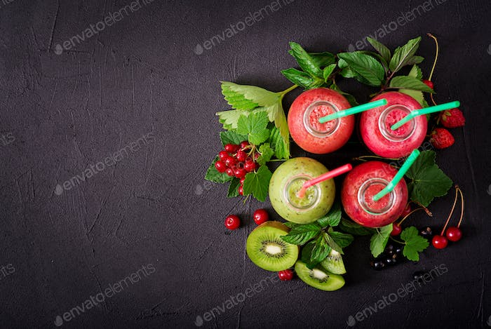 Fresh healthy smoothies from different berries on a dark background. Flat lay. Top view.
