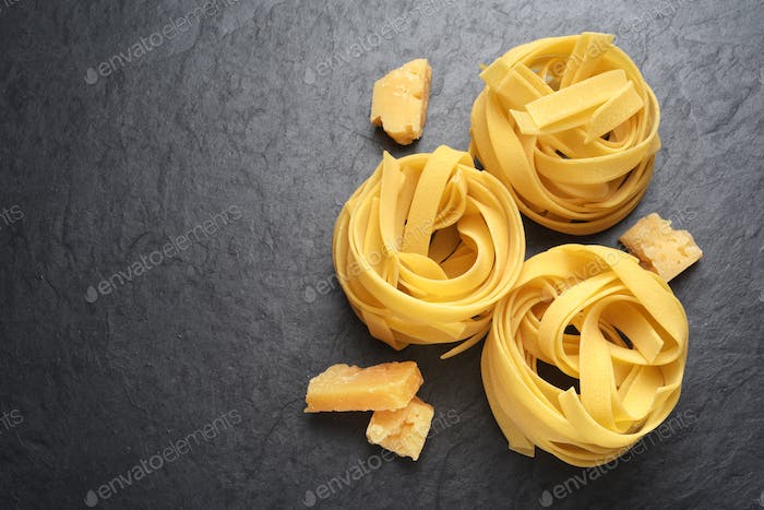 Fettuccine pasta with Parmesan cheese on black background